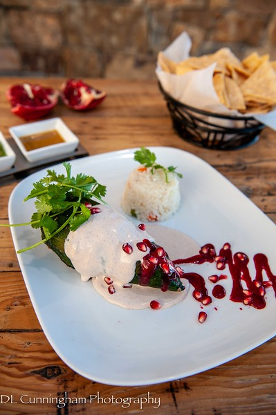 Chile en Nogada~National dish of Mexico. Roasted poblano chile stuffed with beef and pork, raisins, nuts, herbs, white walnut sauce, raspberry sauce.