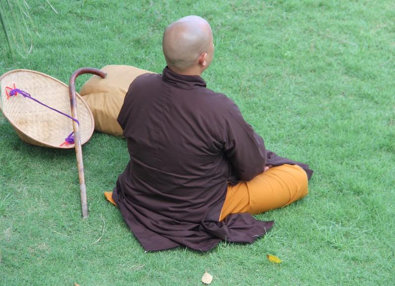 Monk in the hotel garden, meditating