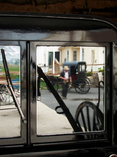 Jason Stolzhus' carriage shop, amazing craftmanship. Reflection of Jason in the window of an Amish cariage. These carriages have wipers, indicators, lights powered by car batteries.