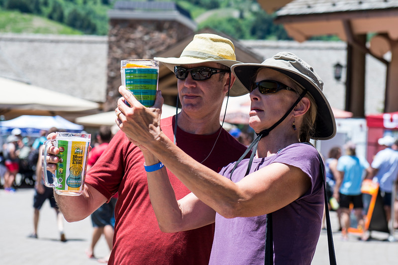 Glenn and Amy McMinn look over their new mugs to see the entire line up of the Blues, Brews, and BBQ Festival at Snowbasin Resort in Huntsville on June 19, 2016. It was the McMinn's first time visiting the festival and they came to see March Fourth who they had seen before and were excited to see the high energy band perform again live.