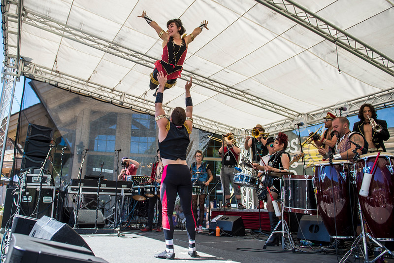 An acrobat soars above the stage as part of the performance by the band March Fourth during the Blues, Brews, and BBQ Festival at Snowbasin Resort in Huntsville on June 19, 2016.