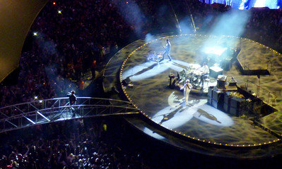 Bono walking over one of two movable bridges that connected center stage to outer.