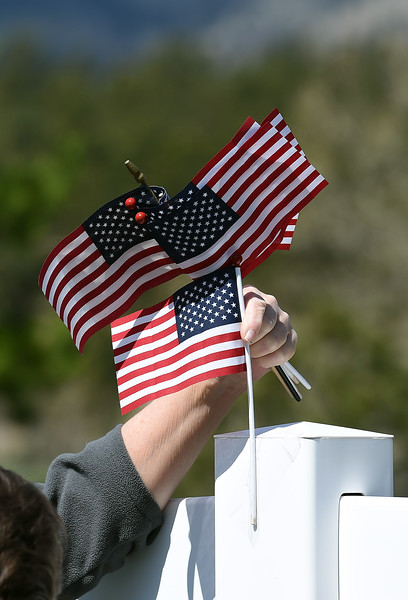 Rue Melbourne, a neighbor of the Conde Family who's son, Gabriel, was killed in Afghanistan this week, attaches an American flag to a fence Friday, May 4, 2018, along Ranch Road in their neighborhood near Carter Lake west of Loveland. Neighbors decided to decorate the area with American flags and patriotic ribbon to honor Gabriel Conde and his family. (Photo by Jenny Sparks/Loveland Reporter-Herald)
