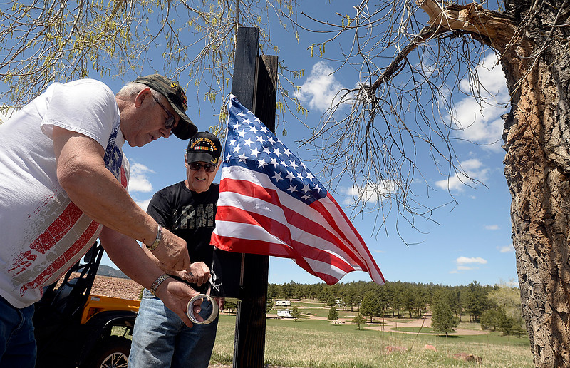 Dennis Henneberg, left, and Martin Treml, center, neighbors of the Conde Family who's son, Gabriel, was killed in Afghanistan this week, hang an American flag Friday, May 4, 2018, along Ranch Road in their neighborhood near Carter Lake west of Loveland. Neighbors decided to decorate the area with American flags and patriotic ribbon to honor Gabriel Conde and his family. (Photo by Jenny Sparks/Loveland Reporter-Herald)