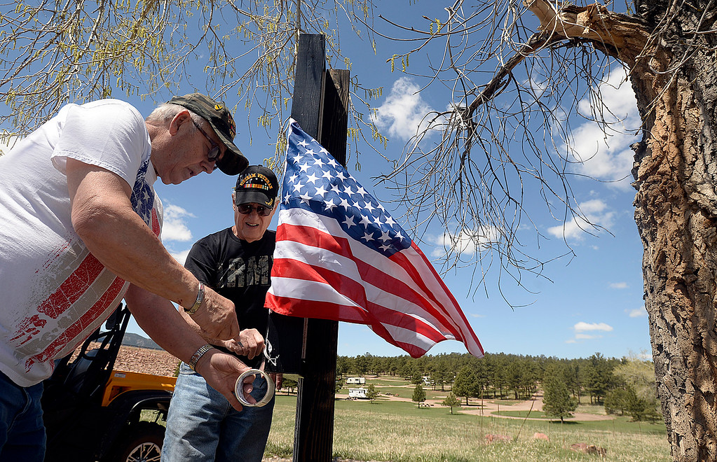 . Dennis Henneberg, left, and Martin Treml, center, neighbors of the Conde Family who\'s son, Gabriel, was killed in Afghanistan this week, hang an American flag Friday, May 4, 2018, along Ranch Road in their neighborhood near Carter Lake west of Loveland. Neighbors decided to decorate the area with American flags and patriotic ribbon to honor Gabriel Conde and his family. (Photo by Jenny Sparks/Loveland Reporter-Herald)