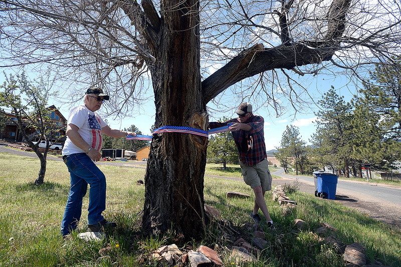Dennis Henneberg, left, and Jeff Shepit, right, neighbors of the Conde Family who's son, Gabriel, was killed in Afghanistan this week, wrap patriotic ribbon around a tree Friday, May 4, 2018, along Ranch Road in their neighborhood near Carter Lake west of Loveland. Neighbors decided to decorate the area with American flags and patriotic ribbon to honor Gabriel Conde and his family. (Photo by Jenny Sparks/Loveland Reporter-Herald)