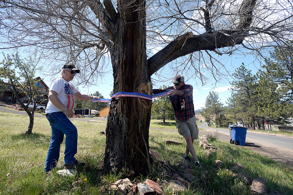 . Dennis Henneberg, left, and Jeff Shepit, right, neighbors of the Conde Family who\'s son, Gabriel, was killed in Afghanistan this week, wrap patriotic ribbon around a tree Friday, May 4, 2018, along Ranch Road in their neighborhood near Carter Lake west of Loveland. Neighbors decided to decorate the area with American flags and patriotic ribbon to honor Gabriel Conde and his family. (Photo by Jenny Sparks/Loveland Reporter-Herald)