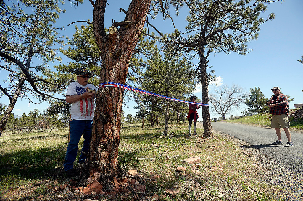 . Dennis Henneberg, left, Teryl Shepit, center right, and Jeff Shepit, right, neighbors of the Conde Family who\'s son, Gabriel, was killed in Afghanistan this week, wrap patriotic ribbon around a tree Friday, May 4, 2018, along Ranch Road in their neighborhood near Carter Lake west of Loveland. Neighbors decided to decorate the area with American flags and patriotic ribbon to honor Gabriel Conde and his family. (Photo by Jenny Sparks/Loveland Reporter-Herald)