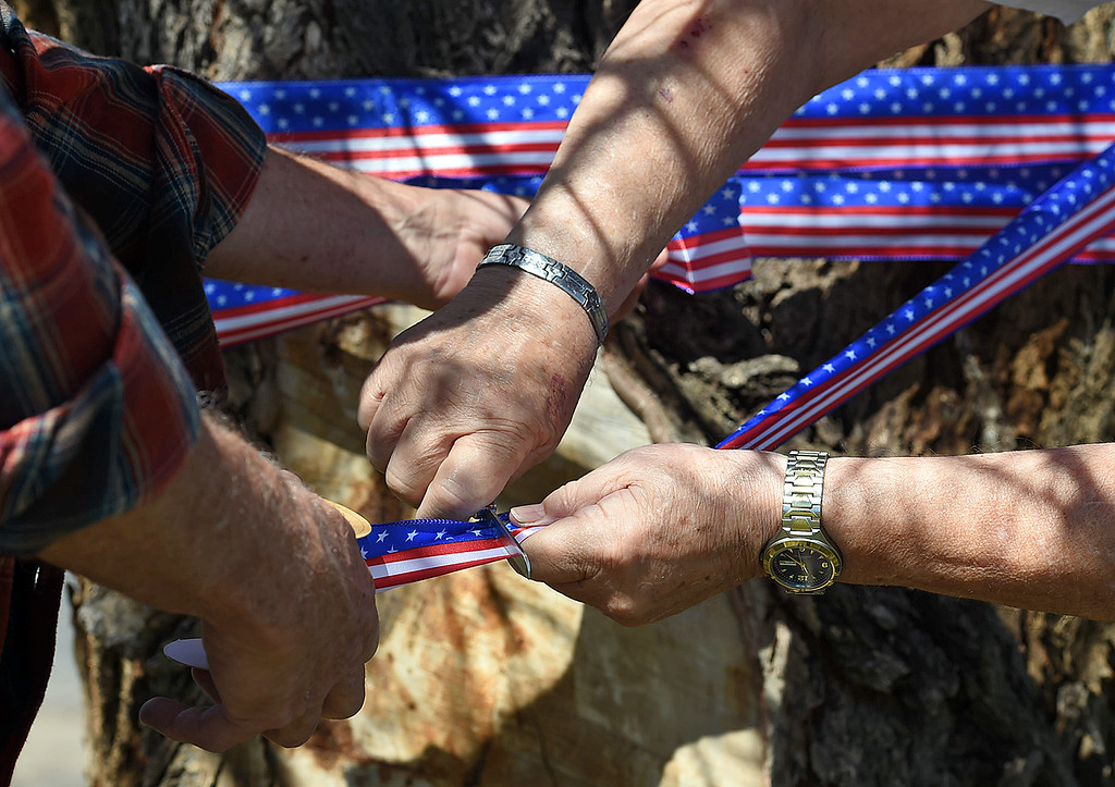 . Jeff Shepit, left, and Dennis Henneberg, right, neighbors of the Conde Family who\'s son, Gabriel, was killed in Afghanistan this week, wrap patriotic ribbon around a tree Friday, May 4, 2018, along Ranch Road in their neighborhood near Carter Lake west of Loveland. Neighbors decided to decorate the area with American flags and patriotic ribbon to honor Gabriel Conde and his family. (Photo by Jenny Sparks/Loveland Reporter-Herald)