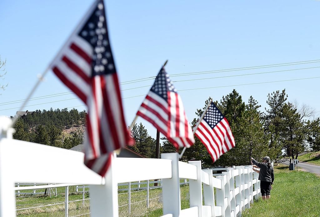 . Rue Melbourne and Marlene Henneberg, neighbors of the Conde Family who\'s son, Gabriel, was killed in Afghanistan this week, attach American flags to a fence Friday, May 4, 2018, along Ranch Road in their neighborhood near Carter Lake west of Loveland. Neighbors decided to decorate the area with American flags and patriotic ribbon to honor Gabriel Conde and his family. (Photo by Jenny Sparks/Loveland Reporter-Herald)