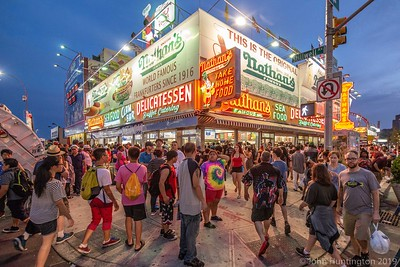 July 4, 2018/ Coney Island, Brookyn, NY People walk in front of Famous Nathan's hotdog on a hot summer July 4th evening.