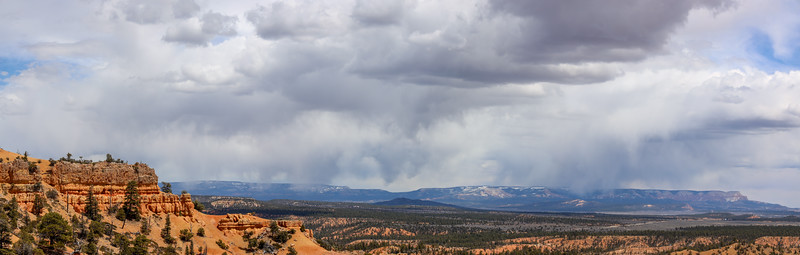 Red Rock Sandstone Cliffs Above Forest Below Storm Clouds From Thunder Mountain Trail in Utah