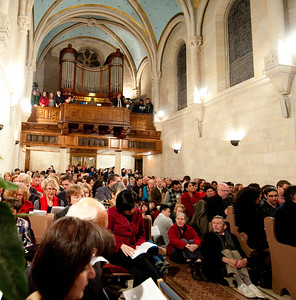 The congregation gathers together--in pews, on the floor, in the balcony, and at the back, to hear the Christmas Eve message at the Evangelical Lutheran Christmas Church in Bethlehem.
