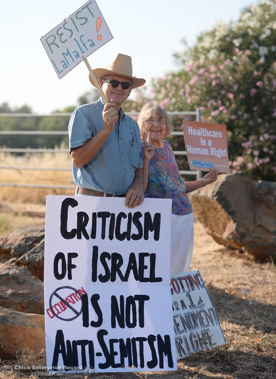 . David Hopper of Paradise and Carol Eberling of Chico stand near the parking lot with sign prior to a Town Hall meeting held by Congressman Doug LaMalfa at the Elks Lodge in Chico, Calif. Monday Aug. 7, 2017.  (Bill Husa -- Enterprise-Record)
