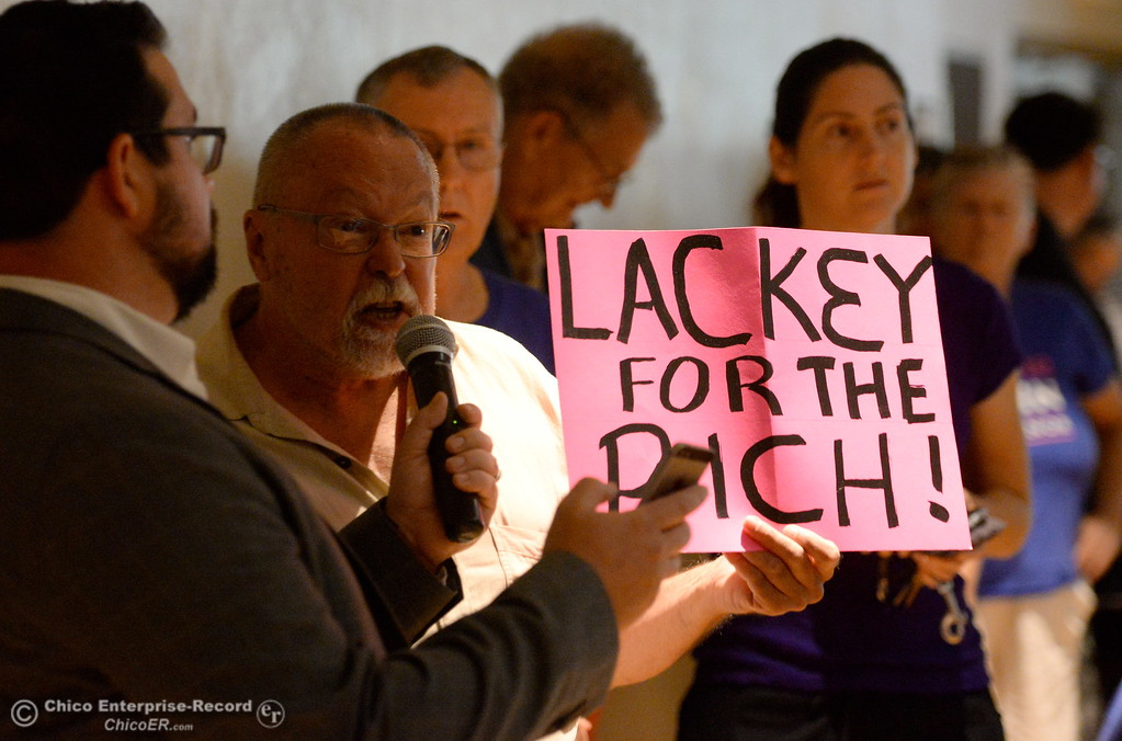 """. A man holds a sign saying \""""Lackey for the Rich\"""" as he makes a comment during a Town Hall meeting held by Congressman Doug LaMalfa at the Elks Lodge in Chico, Calif. Monday Aug. 7, 2017.  (Bill Husa -- Enterprise-Record)"""