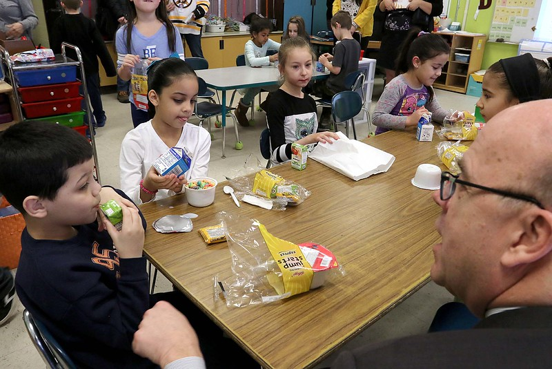 """Congressman Jim McGovern visited Frances Drake Elementary School in Leominster on Friday morning to get a look at how they  serve breakfast to the students because it is """"National School Breakfast Week."""" McGovern chats with first grade students Dereck Ortis-Torres, Ginelyz Ortiz-Torres, Haley Vaden Hastings and others about their breakfasts during his visit. SENTINEL & ENTERPRISE/JOHN LOVE"""