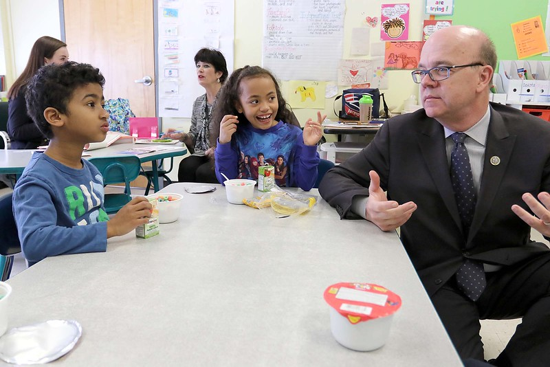 """Congressman Jim McGovern visited Frances Drake Elementary School in Leominster on Friday morning to get a look at how they  serve breakfast to the students because it is """"National School Breakfast Week."""" McGovern chats with first graders Christopher Marte and Victoria Swift during his visit. SENTINEL & ENTERPRISE/JOHN LOVE"""