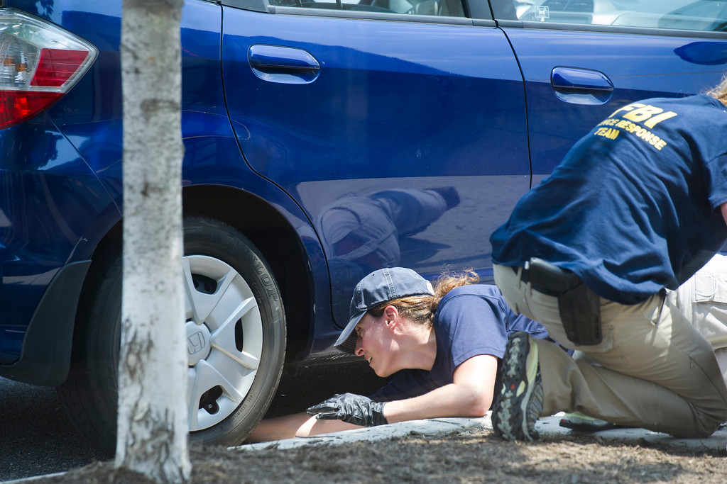 . A FBI Evidence Response Team member mark evidence under a car at the scene of a multiple shooting in Alexandria, Va., Wednesday, June 14, 2017, involving House Majority Whip Steve Scalise of La., and others, during a congressional baseball practice. (AP Photo/Cliff Owen)