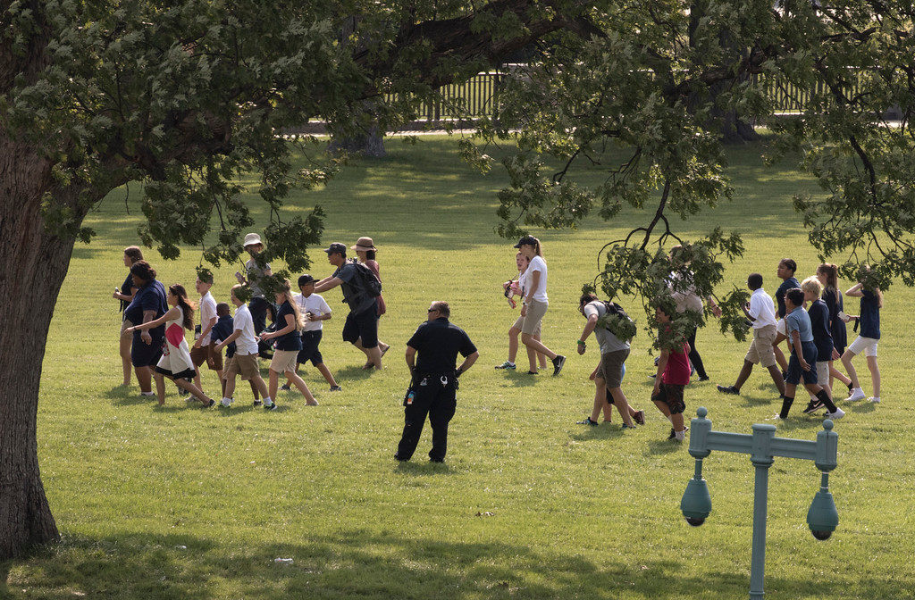 . Tourists are directed away from the Capitol Building and across the lawn by Capitol Hill Police officers, Wednesday, June 14, 2017, after House Majority Whip Steve Scalise of La. was shot at a Congressional baseball practice in Alexandria, Va.  (AP Photo/J. Scott Applewhite)