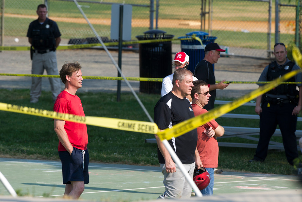 . Members of the Republican Congressional softball team stand behind police tape in Alexandria, Va., Wednesday, June 14, 2017, after a multiple shooting involving House Majority Whip Steve Scalise of La. during a Congressional baseball practice. (AP Photo/Cliff Owen)