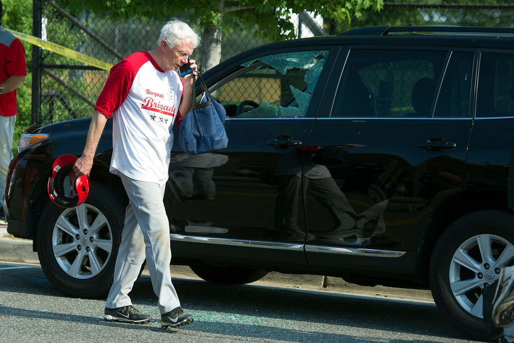 . Rep. Jack Bergman, R-Mich. talks on the phone while walking past a damaged vehicle at a shooting scene where House Majority Whip Steve Scalise of La. was shot at a Congressional baseball practice, Wednesday, June 14, 2017, in Alexandria, Va.  (AP Photo/Cliff Owen)