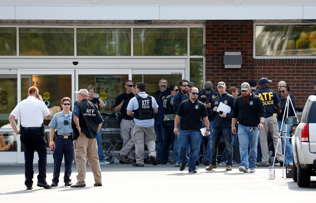 . Law enforcement officers gather near the scene of a shooting near a baseball field in Alexandria, Va., Wednesday, June 14, 2017, where House Majority Whip Steve Scalise of La. was shot during a congressional baseball practice. (AP Photo/Alex Brandon)
