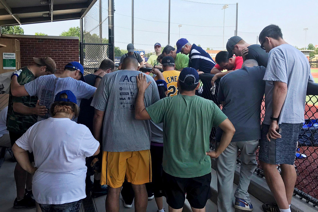 . House Democrats at a baseball field in Washington pray for their colleagues after hearing that a gunman fired on Republican lawmakers at a baseball practice in Alexandria, Va., Wednesday, June 14, 2017. A rifle-wielding attacker wounded House GOP Whip Steve Scalise of Louisiana and several others as congressmen and aides dove for cover. (Rep. Ruben J. Kihuen via AP)
