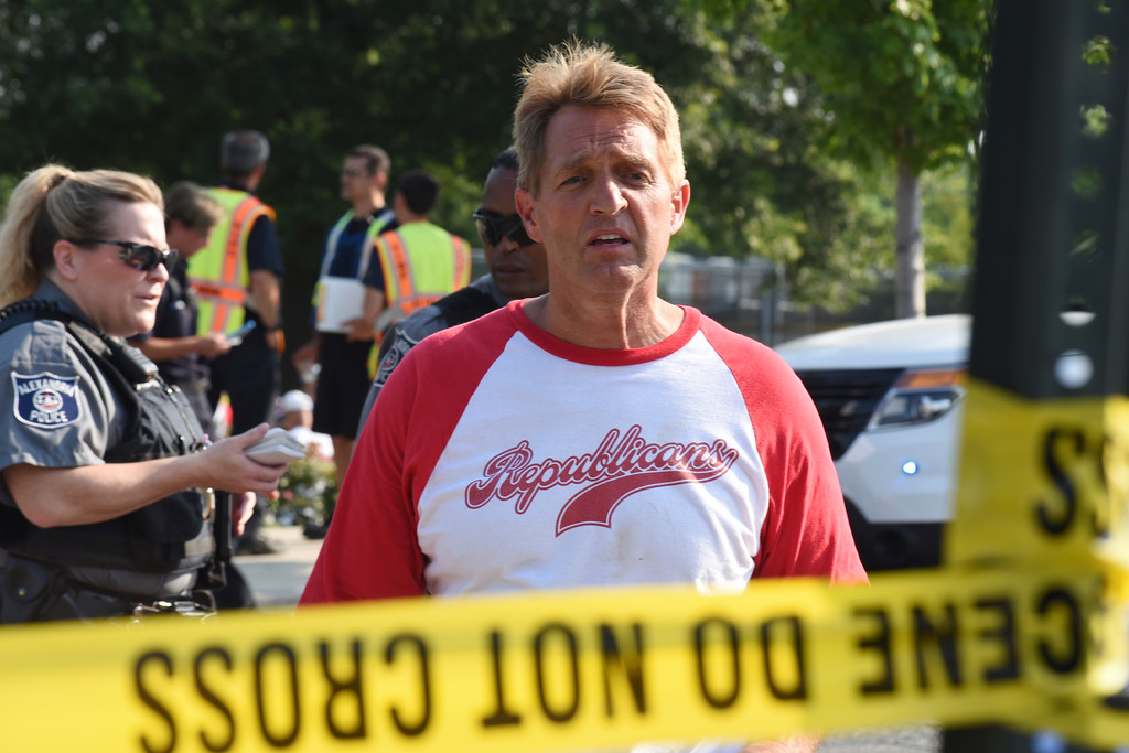 . Sen. Jeff Flake, R-Ariz. walks toward media gathered at the scene of a shooting at a baseball field in Alexandria, Va., Wednesday, June 14, 2017, during a Congressional baseball practice where House Majority Whip Steve Scalise of La. was shot. (AP Photo/Kevin S. Vineys)