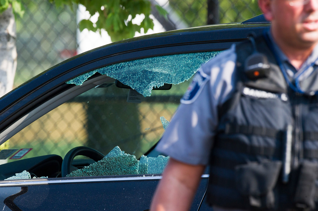 . A police officer stands by an automobile with a damaged driver\'s window at the scene of a multiple shooting in Alexandria, Va., Wednesday, June 14, 2017, where House Majority Whip Steve Scalise of La. was shot.  (AP Photo/Cliff Owen)