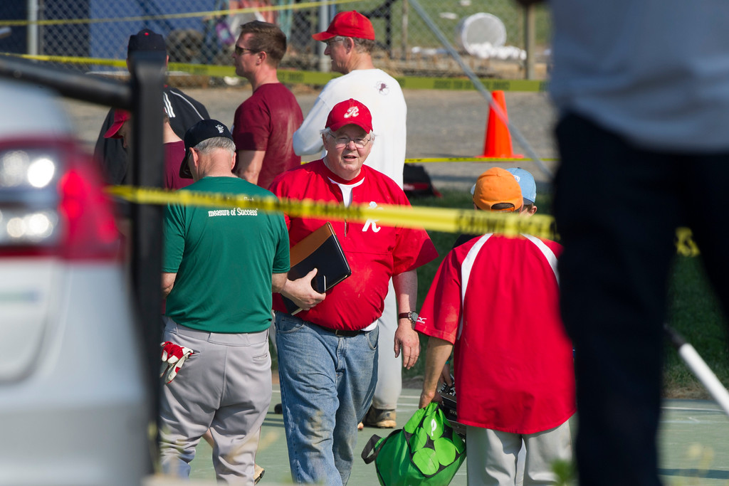 . Rep. Joe Barton, R-Texas, center, and other members of the Republican Congressional softball team, stand behind police tape of the scene of a multiple shooting in Alexandria, Va., Wednesday, June 14, 2017, where House Majority Whip Steve Scalise of La. was shot. (AP Photo/Cliff Owen)