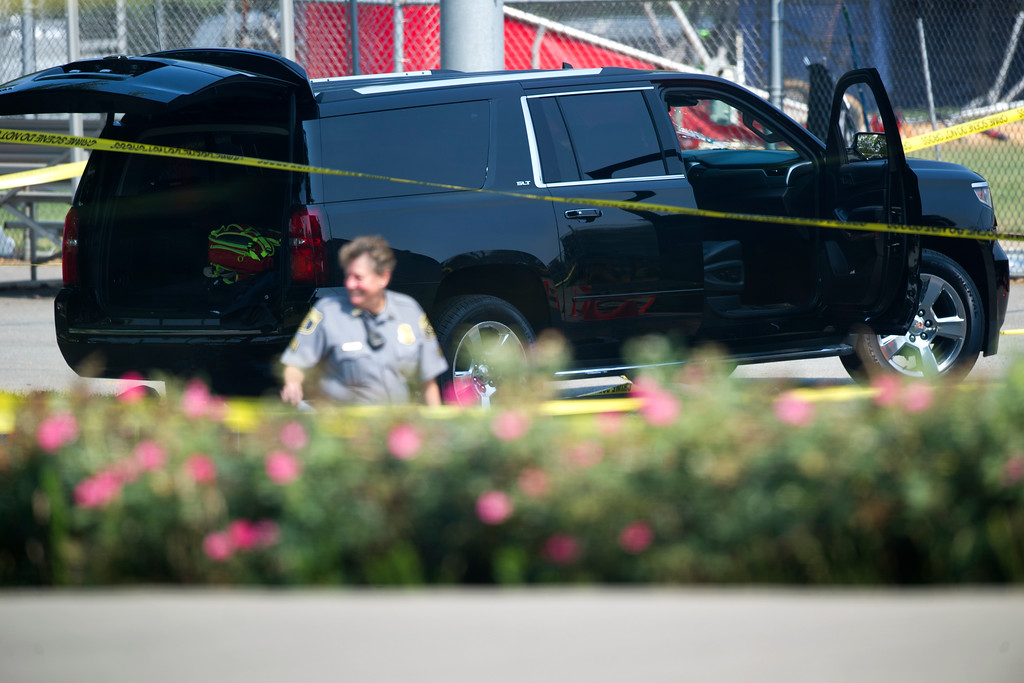. An SUV sits with its doors open in the parking lot of the ball field in Alexandria, Va., Wednesday, June 14, 2017, where there was a multiple shooting involving a House Majority Whip of La. during a Congressional baseball practice. (AP Photo/Cliff Owen)