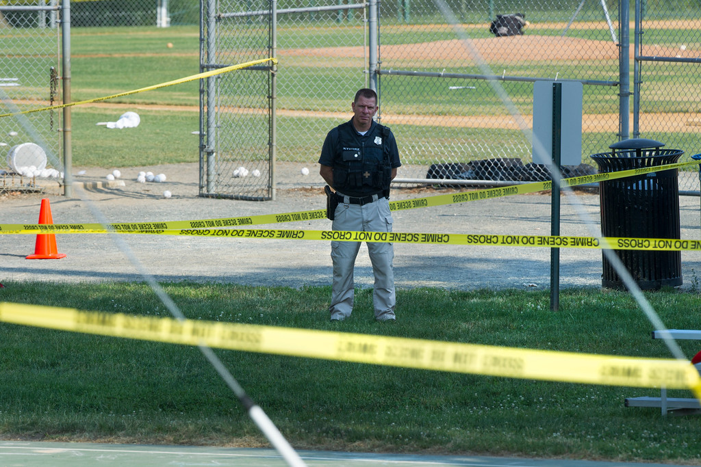 . A police office stands watch behind police tape near strewn softballs on a field in Alexandria, Va., Wednesday, June 14, 2017, after a multiple shooting involving House Majority Whip Steve Scalise of La. (AP Photo/Cliff Owen)
