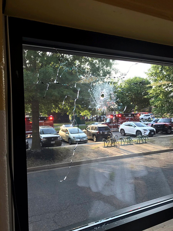 . Emergency personnel are seen through a window with a bullet hole in Alexandria, Va., Wednesday, June 14, 2017. House Majority Whip Steve Scalise of Louisiana and others were shot Wednesday at a congressional baseball practice, officials said. (Joseph Miscavige via AP)
