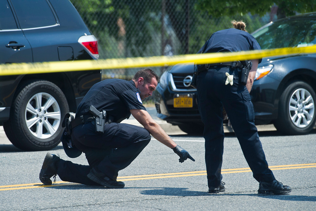 . Crime scene investigators search for evidence at the scene of a multiple shooting in Alexandria, Va., Wednesday, June 14, 2017, where House Majority Whip Steve Scalise of La., and others, were shot during a congressional baseball practice. (AP Photo/Cliff Owen)