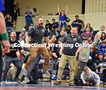 Gilbert assistant wrestling coach Chris Marks leaps in celebration, left, after Andrey Zhovkly won a Class S championship at 195 pounds. Head coach Darek Schibi is on the right.