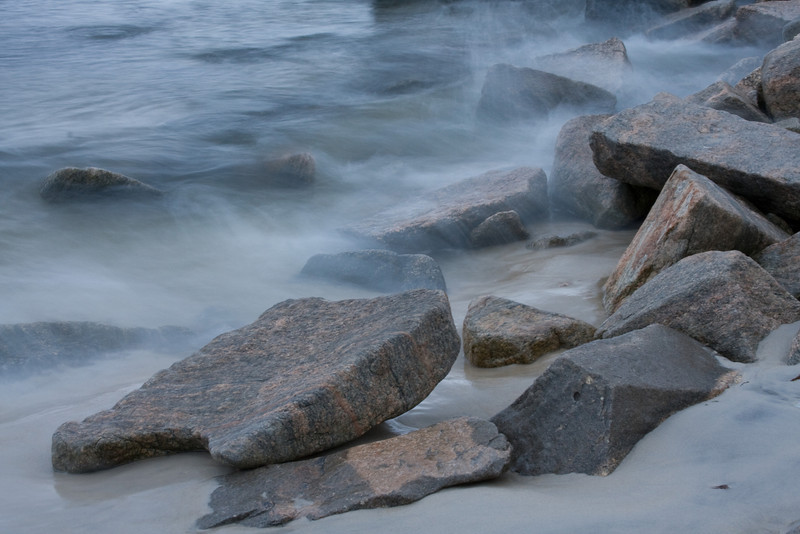 A slow shutter speed blurred the water while maintaining sharpness in the rocks along the shore.