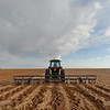 """A tractor is pulling an implement called a """"sand fighter"""" to help the soil form dirt clods to prevent erosion. This practice is primarily done on continuous cotton fields to keep the top soil from blowing away -- Lynn County, Texas."""