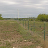 Two conservation and energy efforts working together - cross fencing and wind turbines - at Stasney's Cook Ranch in Albany, Texas.