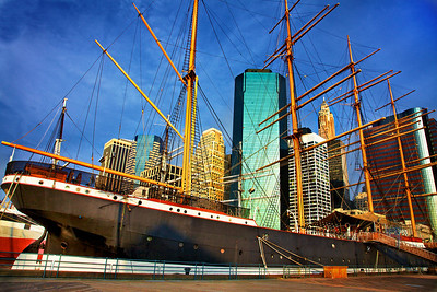 The early morning sun lits the Lower Manhattan skyline and the Peking sailing ship berthed at the South Street Seaport Museum (Pier 17.) The ship was built in Germany in 1911 but was moored in England for over 40 years until it was brought to this museum in 1975.