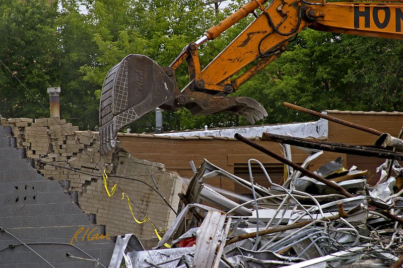Building construction demolition. Samsung SE 350 LC2 backhoe grapple shovel breaks up and pulls brick vineer off concrete block building wall.  YMCA, Ann Arbor, 2003