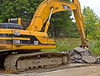 Asphalt construction, demolition: Caterpillar 330BL crawler mounted hydraulic boom backhoe excavator lifts broken asphalt pavement pieces and loads them on rear dump truck to be hauled to an asphalt recycling plant. Dixboro Road at Geddes, Ann Arbor, 2005.