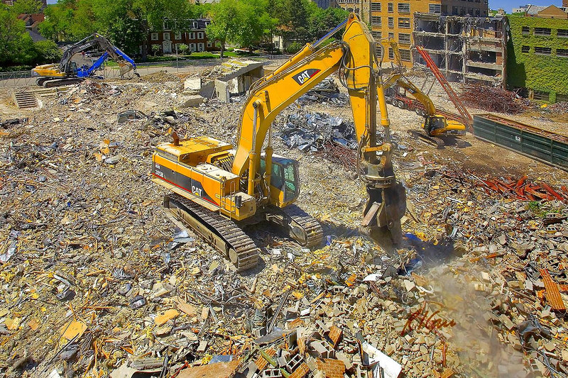 Demolition, construction recycling: Five hydraulic backhoe/excavators separate, sort, and load demolition debris. In foreground, Caterpillar 345BL track mounted hydraulic backhoe excavator fitted with 360 degree rotating hydraulic shear separates and sorts out metal debris into stacks. Business School, University of Michigan, Ann Arbor, May 2006.