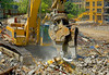 Demolition, construction recycling: Caterpillar 345BL track mounted hydraulic backhoe excavator fitted with 360 degree rotating hydraulic shear separates and sorts out metal debris into stacks. Here it has picked up what seems to be sheet metal item to pile it behind work area. Business School, University of Michigan, Ann Arbor, May 2006.