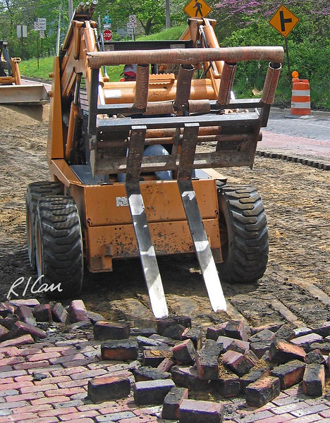 Brick pavement construction demolition: Case 1845C skid steer tractor with forklift attachment has broken loose a segment of brick paver street. Depot Street, Ann Arbor, 2004.