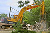 Building construction demolition. Komatsu PC200LC5 crawler mounted backhoe picks up building demolition debris with its grapple. YMCA, Ann Arbor, 2003