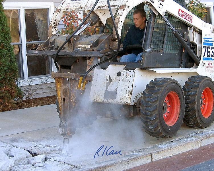 Concrete construction demolition: Bobcat 763 skid steer tractor uses pavement breaker attachment to break up concrete sidewalk. Hawthorne Suites, Chelmsford, Massachusetts, 2003