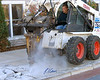 Concrete construction demolition: Bobcat 763 skid steer tractor uses pavement breaker attachment to break up concrete sidewalk. Hawthorne Suites, Chelmsford, Massachusetts, 2003