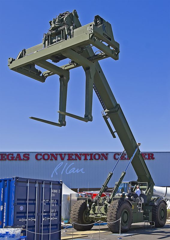 Construction material handling: Kalmar RT 24T 4-wheel drive diesel powered rough terrain container handler (RTCH), United States Marine Corps issue, weighs 54,000 kg / 59 tons, lifts 32 ft / 10 m, and can stack containers 3 high. Level ground max speed is 23 mph / 37 km/h empty, 15 / 24 loaded.  CONEXPO, Las Vegas, Nevada, March 15-19, 2005.