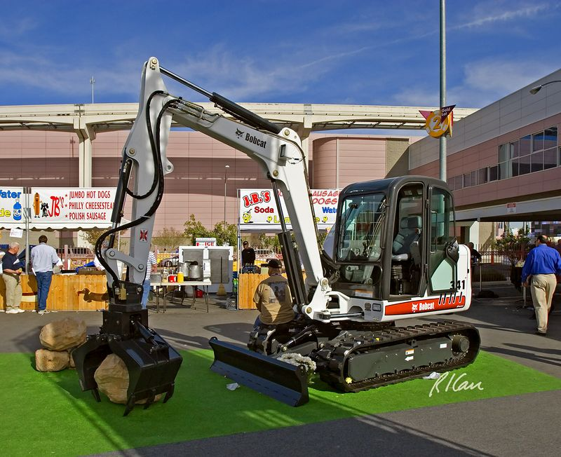 Earthmoving construction: Bobcat 341 crawler mounted compact hydraulic excavator/backhoe with blade. Lift capacity is 2500 lb/ 1150 kg. Mounted on boom is rotating clamshell bucket. CONEXPO, Las Vegas, Nevada, March 15, 2005.