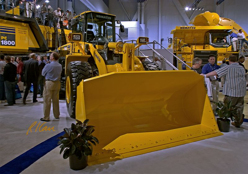 Earthmoving construction: Komatsu WA380 wheel loader, 140 kw / 187 hp, 18,000 kg / 40,000 lb, 4 m3 / 5 yd3 bucket. Behind and towering above the loader is the PC1800 giant mining/ construction backhoe excavator, with people standing on top. CONEXPO, Las Vegas, Nevada, March 15, 2005.